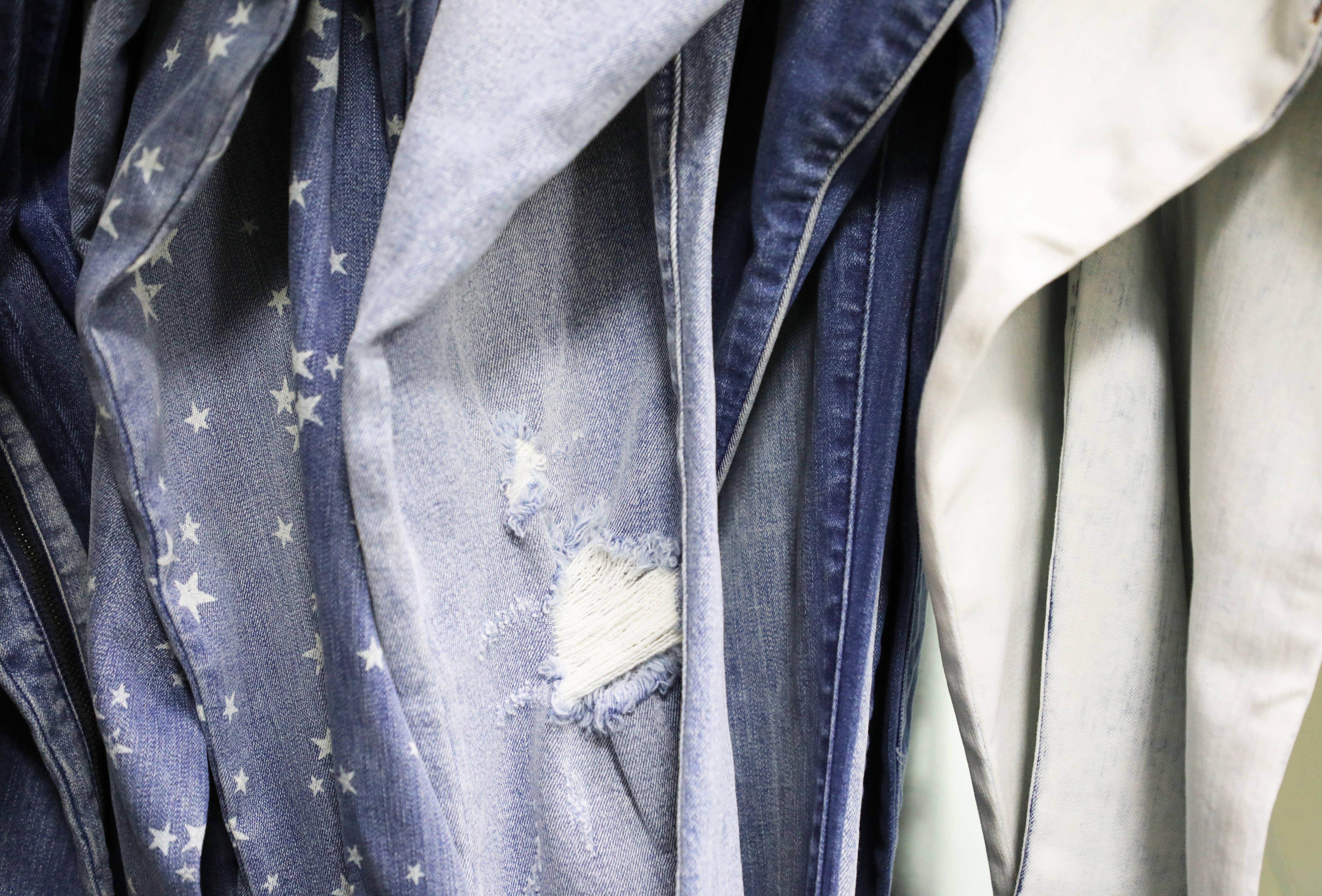 Selection of denim jeans hanging on rack