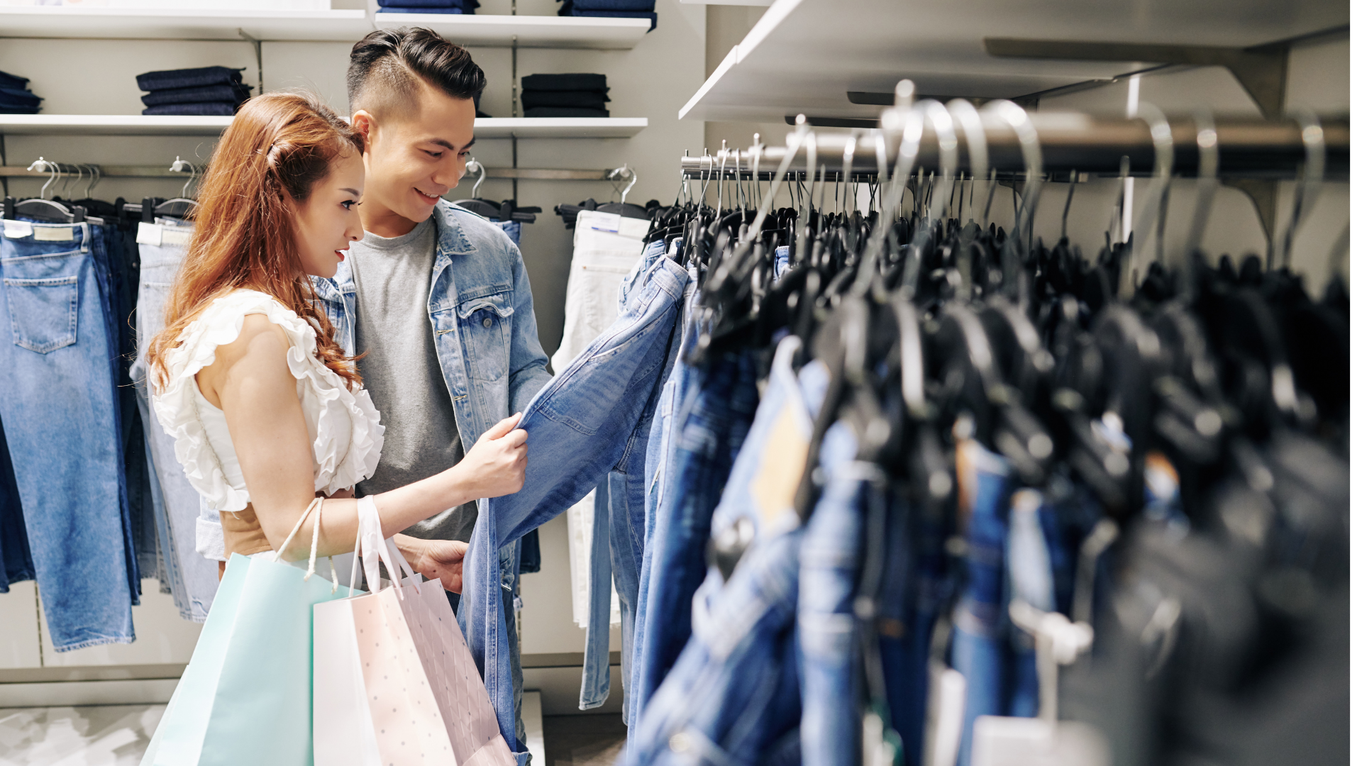 Man and woman looking at a pair of jeans in a retail store.