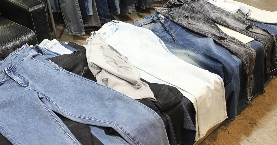 image of an assorted variety of denim jeans in different colours: blues, blacks, creams