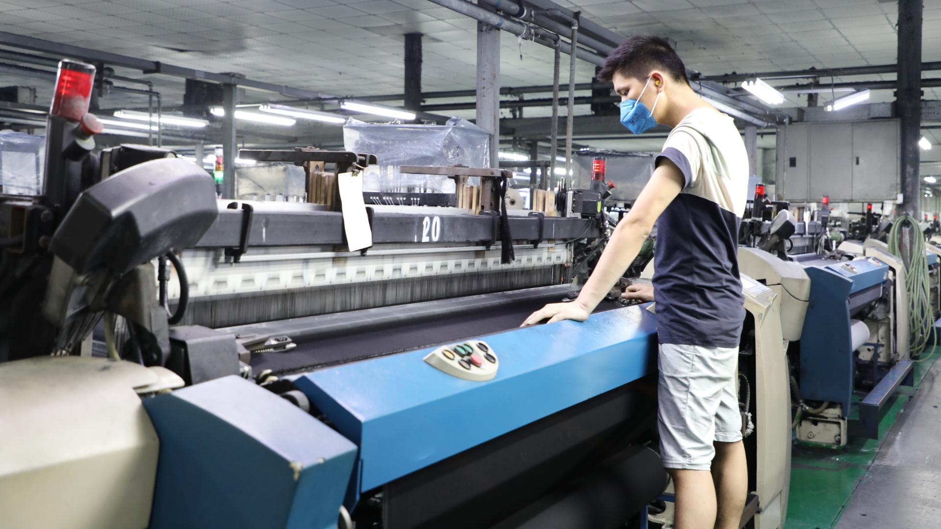 Man working with weaving machine