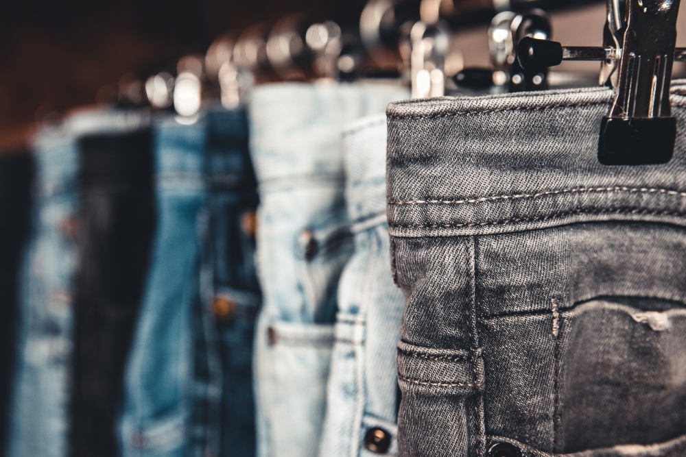 A rack with multiple jeans with different finishes and washes for different looks.